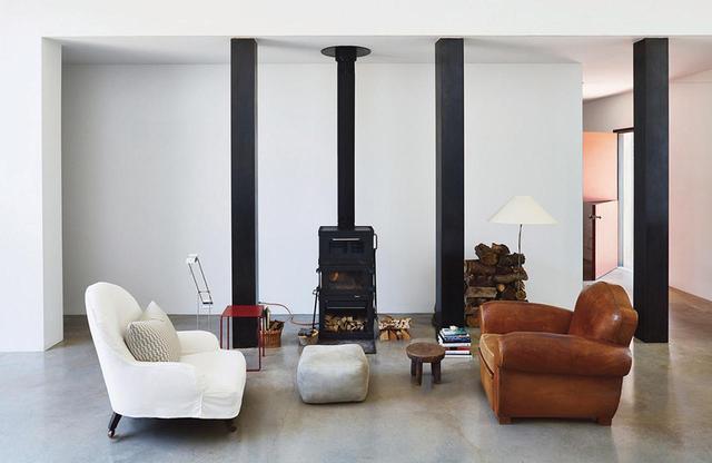 画像: リビングには、カバーをかけたエドワード7世時代の椅子と、1940年代のフランス製のひじ掛け椅子が、ライス社の薪ストーブのそばに置かれている。ランプは1970年代のもので、デザインはそれぞれドイツのリチャード・サッパーとインゴ・マウラー