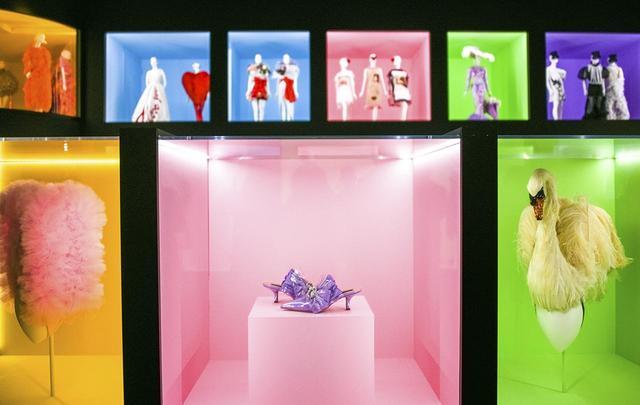 画像: メトロポリタン美術館で開催中の『キャンプ:ファッションについてのノート』展の会場風景。 (手前左から) パム・ホッグによるピンクのナイロン・チュールのヘッドピース、アダ・ココサールによる「マリー・アントワネット」ミュール、ジャイルズ・ディーコンとスティーヴン・ジョーンズによるヘッドピース