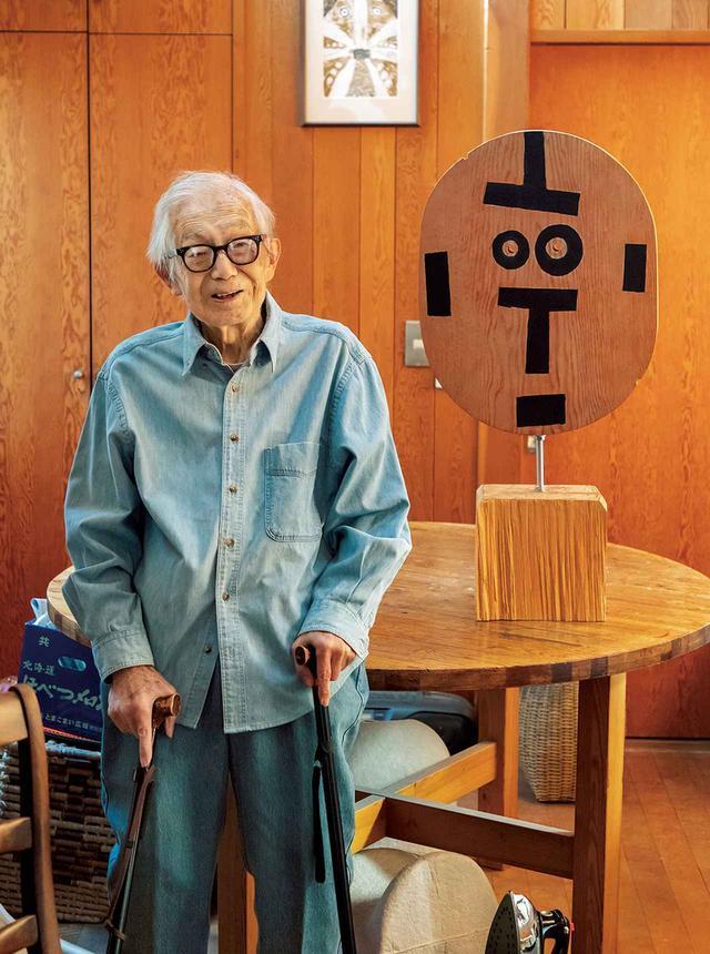 画像: 自宅のアトリエにて。写真右のオブジェは自画像。96歳にして初めて手がけた木工作品。ずっと木工をやりたいと思って自宅の改修工事のときに天板をとっておいた