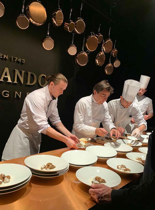 画像: 会場内のキッチン・カウンターで盛り付けをするヤニック・アレノシェフ(左から2番目)。スカモルツァチーズのソースをからめたアミガサ茸にイラン産のブラックレモンとオレンジパウダーを添えたひと皿は、2軒のレストランで三ツ星をもつアレノシェフの面目躍如というべき素晴らしさだった PHOTOGRAPH BY JUNKO ASAKA