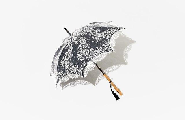 画像: 日傘 <生地:麻100%、レース:綿75%・ナイロン25%、全長83㎝>¥150,000 楓の持ち手に、繊細なレースを濃紺の麻に重ねた日本製の日傘。繊細で華麗な総レース仕上げと優雅なフォルムは、日本の職人の手仕事の秀逸さと底力が伝わる和光ならではの1本だ。開けば華やかで、陽ざしの影までが美しく、閉じればキリっと細身に。エレガンスの真髄を体現するデザインは、ジュエリーのような存在だ