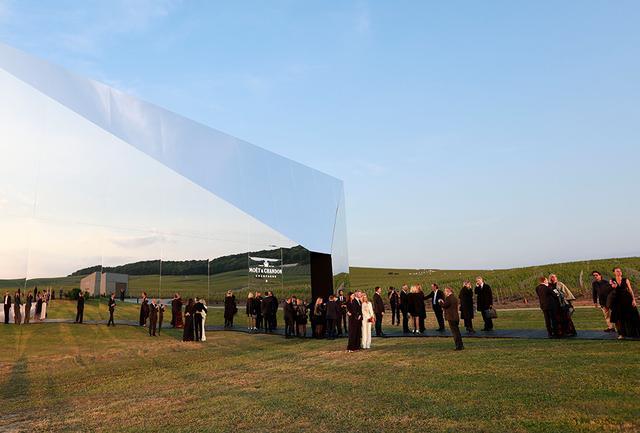 画像: この日のためだけに作られた鏡張りのディナー会場。暮れかかる夕日を映して燦然と輝いていた