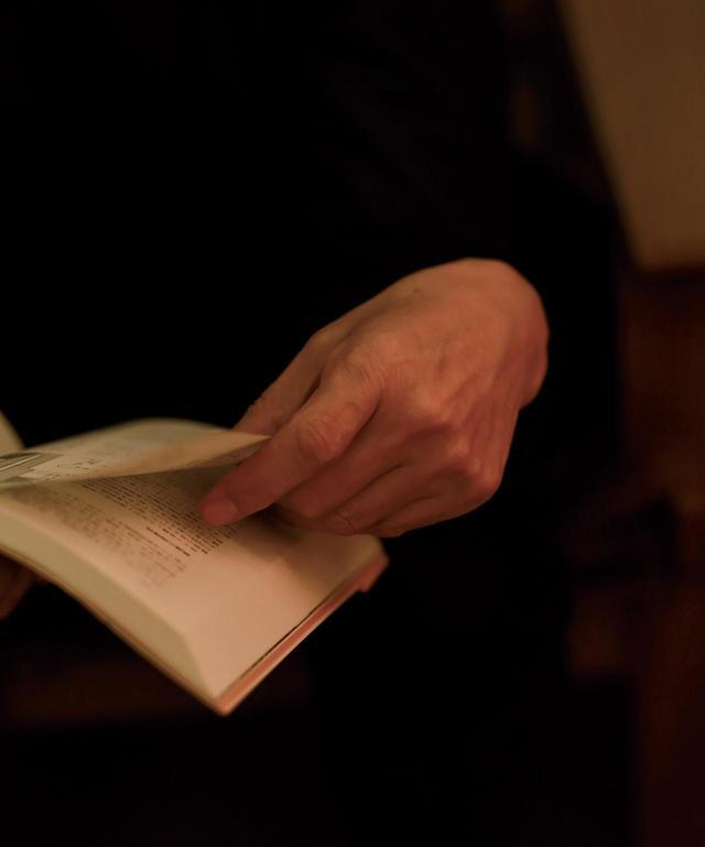 """画像: 本を読む時間を五感で味わえる設えに。坂本図書の室内で手に取った本のページをめくる坂本さん。 「本には""""もの""""としてのよさもあると思います。表紙や背のたたずまいの美しさを眺めるのも好きですし、必ず一度カバーをはずして中表紙も綴じ方もチェックします。本の匂いも嗅ぎます」"""