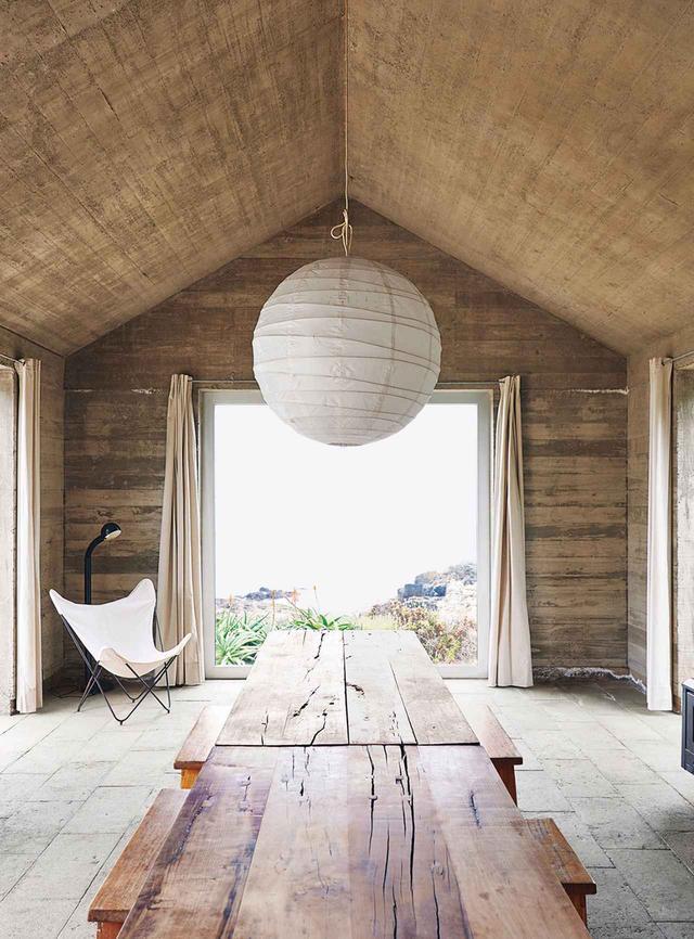 画像: ロスビロスのバイアアスールにある、セシリア・プガ設計の家。普通の家の形をした3つのコンクリート製の箱を組み合わせ、ほかの二つの上にひとつの家が逆さまに乗った形をしている。照明はイサム・ノグチのデザイン、バタフライチェアはノール製