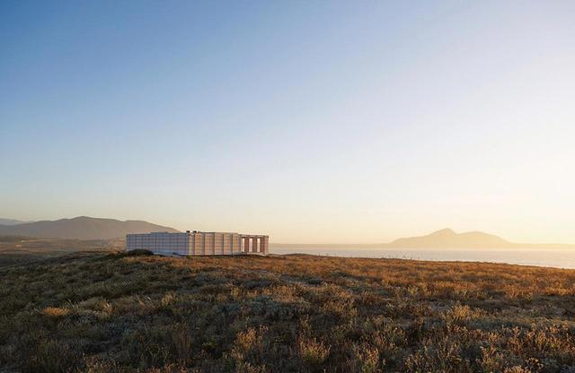 画像: クリスティアン・イスキエルドが2015年にコキンボの近くのプラヤブランカに建てた家。湿地を望む砂丘の上に建つ。松材を用いた構造物に4枚の羽根のような扉と3つの寝室、居間がひとつある
