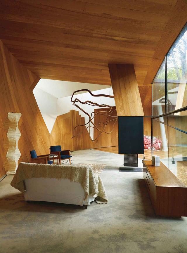 画像: スミルハン・ラディックがデザインした「正しい角度について書かれた詩のための家」。ボリビア産の針葉樹材に囲まれた居間に、鋭角の明かり取り窓を通して日光が差し込む。《ドローイング》と題されたマルセラ・コレア作の彫刻が1960年代の椅子の上に吊り下がり、スリップカバーがかかったソファが暖炉に面している