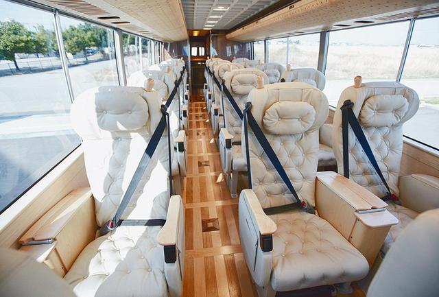 画像: シートは体を包み込むような形状とクッション性、革の質感など、バスとは思えない座り心地のよさ。シートの背面にある革製ポケットは豊岡の職人によるもので、小さな書斎のように使い勝手よくカスタマイズできる。床やフットレストも肌触りのいい木製 COURTESY OF SHINKI BUS