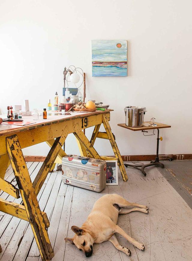 画像: 織物工場にあるアルカレーのスタジオ。画家のジュディス・クラインとスペースを共有している。ハリケーンで壊れた障壁を再利用して作られたデスク。壁にはクラインの作品が飾られている