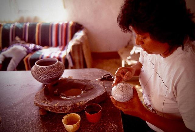 画像: 土器の絵付け。フリーハンドで自然のモチーフを描いてゆく