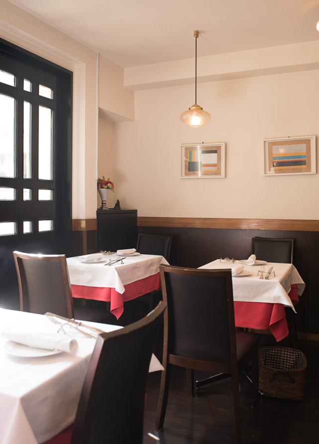 画像: クロスのかかったテーブルに、アーティスト作品が飾られた壁。昼は自然光も入り、温かな空気が流れる