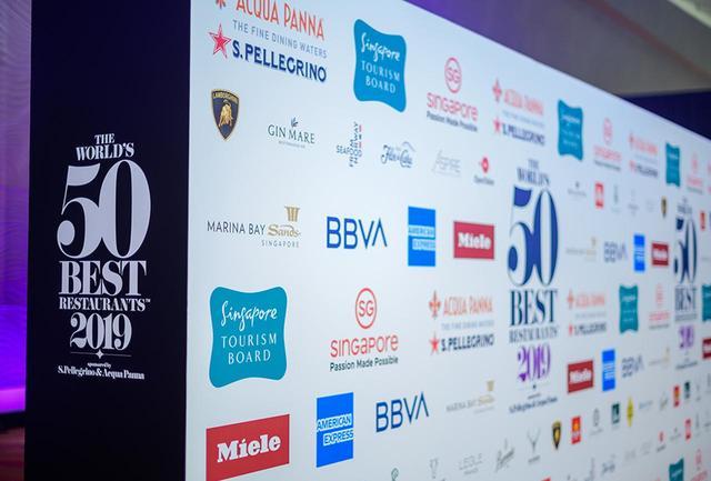 画像: 「The World's 50 Best Restaurants 2019」の舞台となったシンガポールのマリーナベイサンズのカクテルレセプション会場に設けられた、フォトコールの背景。ワインやビール、プレミアムジンやウイスキーなどの飲料、クレジットカードや銀行や車、チーズやハムやビーフ、キッチンや食器など、スポンサー&パートナー企業は20を超える
