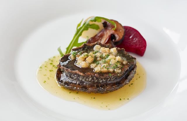 画像: 「鮑ステーキ こがしバターソース」 先々代総料理長から続く手法により大根と一緒に下茹ですることで、独特のしっとりむっちりした食感になる