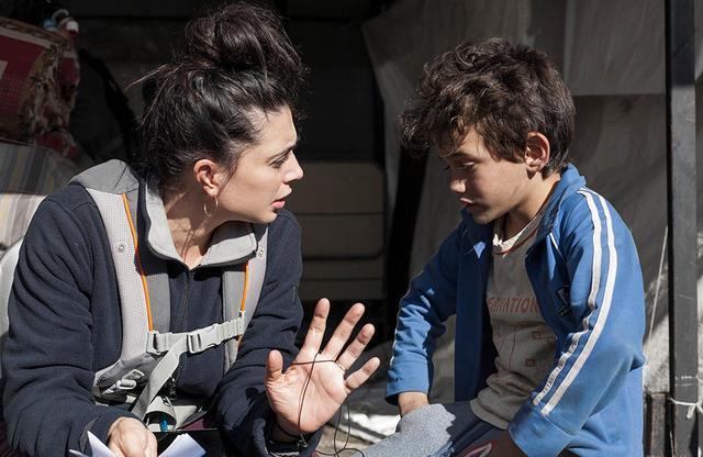 画像: モニターを赤ちゃんの抱っこ紐で背中に括り付けて撮影中のラバキー監督。ヨナスと同年代の娘のため、撮影の合間に帰宅して授乳する日々が続いたという。「睡眠時間がほとんど取れなかったとしても、撮影中はずっと、得体の知れない力がみなぎる素晴らしい体験だった」と語っている © 2018MoozFilms / © Fares Sokhon