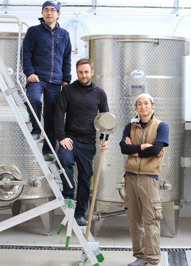 画像: 現地の酒蔵は、法律の関係で床や壁はコンクリートにしなくてはならないが、室や甑、舟場など、日本と変わらない設備が整っている。蔵の設立当初から2018年の酒造りまで杜氏を務めた若山健一郎さん(左)、現在の杜氏である田中光平さん(右)らとともに、この地ならではの日本酒をつくる COURTESY OF LES LARMES DU LEVANT