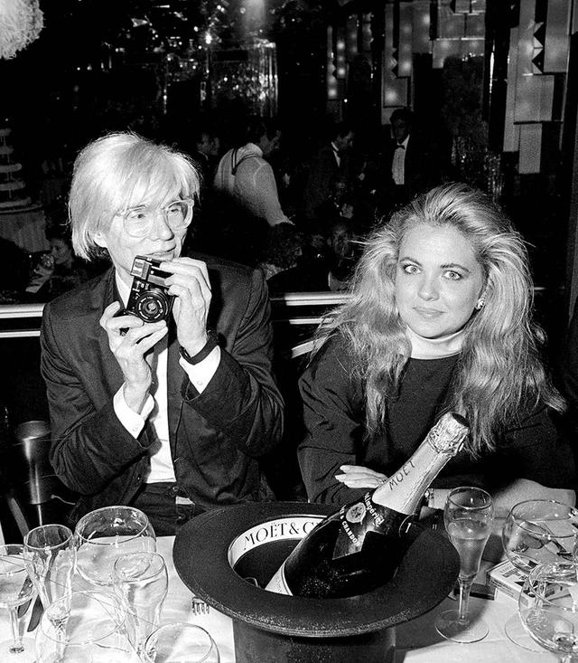 画像: 1985年、カメラを手にするアンディ・ウォーホル。帽子型のシャンパン・クーラーがアーティスティック © Ron Galella