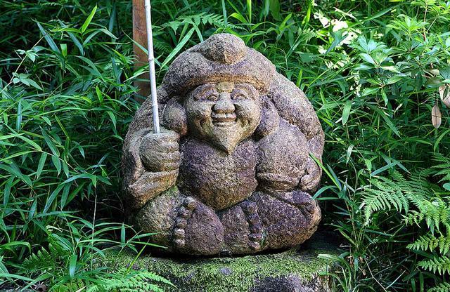 画像: 江戸中期の画家、伊藤若冲(いとう じゃくちゅう)の下絵による五百羅漢のうちの約20体が庭園に点在。ほかは京都・伏見の石峰寺に置かれている。写真は七福神の恵比寿様
