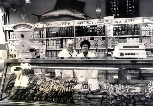 画像: 店の創業者ジョエル・ラスの3人の娘の1人であるアン・ラス・フェダーマン(右)と夫のハーブ・フェダーマン。1960年代にはカウンターから、白身魚、鮭の燻製、その他の珍味を提供していた COURTESY OF RUSS & DAUGHTERS
