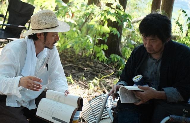 画像: 脚本を手に語り合う、マタギ役の永瀬正敏(右)とオダギリ監督 © 2019「ある船頭の話」製作委員会