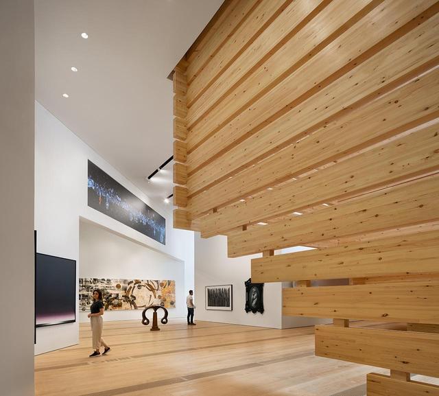 画像: 美術館の1階展示スペース。梁が表出した場所にはモニターを設置するなど、建築空間に合わせて作品が配置されている © NAARO