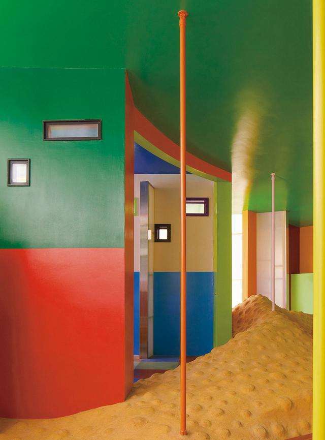 画像: 荒川修作&マドリン・ギンズの設計によるニューヨーク州イースト・ハンプトンにある≪バイオスクリーブ・ハウス:寿命を延ばす家≫(2008年)。土を固めた凸凹の床や強烈な色彩の壁は住みにくくするための工夫。おかげで命を延ばすことができる