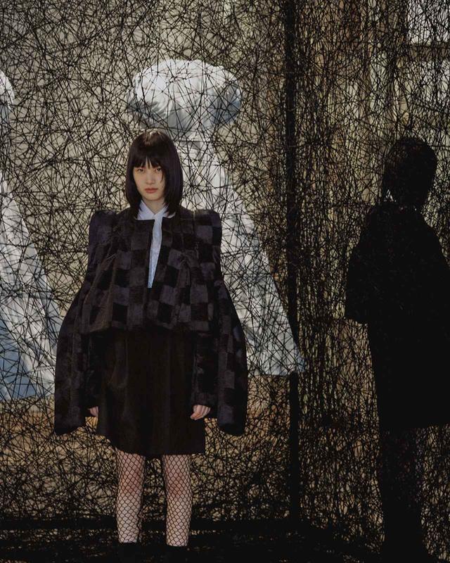 画像: ≪時空の反射≫(2018年) 衣服は人にとって第二の皮膚。鉄枠に囲まれた黒い糸の空間に浮かぶドレスは、着る人の不在を示唆する。そして空間を半分に仕切る鏡が、ドレスとともに不在を増幅させる ジャケット¥179,000、ブラウス¥38,000、パンツ¥39,000、シューズ¥65,000、レギンス¥28,000 コム デ ギャルソン TEL.03(3486)7611