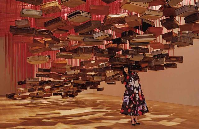 画像: ≪集積―目的地を求めて≫(2014年/2019年) 赤い糸で吊るされた約440個のスーツケース。蚤の市で見つけたスーツケースは震え、カタカタと音を鳴らす。それは見知らぬ土地へと旅立つ人の、あるいは故郷へと帰る人の胸の高鳴りを表すようだ ワンピース¥592,000、パンプス¥95,000(ともに予定価格) プラダ クライアントサービス(プラダ) フリーダイヤル:0120-451-913