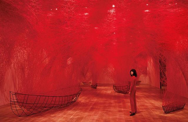 画像: ≪不確かな旅≫(2016年/2019年) 塩田千春にとって赤い糸は、血管や血縁、縁を意味する。赤い糸は絡み合い、解け、また結びつく。舟は見えない先行きの象徴だ。不確かな旅の先にはさまざまな出会いが待っている ニット¥127,000、ニットパンツ¥148,000、ブーツ¥148,000(参考価格)、シルバーリング(左手薬指・参考色)¥38,000、エッフェル塔リング(左手中指・参考色)¥38,000 バレンシアガ ジャパン(バレンシアガ) TEL.0570(000)601
