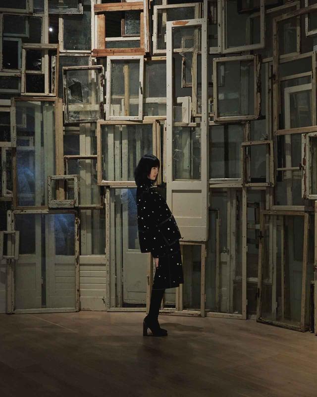 画像: ≪内と外≫(2008年/2019年) 人間の体をとり囲む壁やドアや窓は第三の皮膚。塩田は、ベルリンの壁の崩壊から15年後、再開発に伴い廃棄された窓枠を集め歩いた。打ち捨てられた約230枚の窓枠は、そこに住んでいた人とかつてあった壁の不在へとつながる レザーコート¥2,330,000、レザースカート¥1,010,000、ニット¥220,000、ニーハイブーツ¥262,000 エルメスジャポン(エルメス) TEL.03(3569)3300