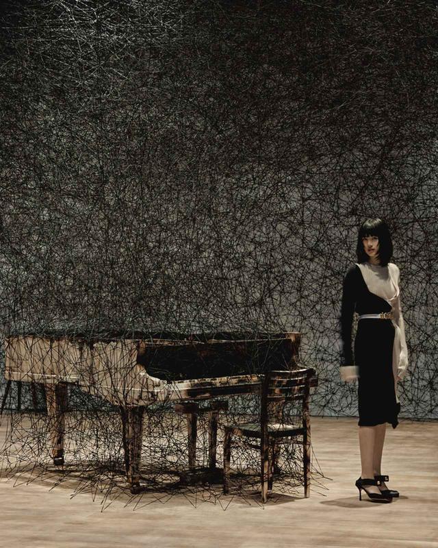 画像: ≪静けさのなかで≫(2002年/2019年) 幼少期に、隣家が夜中に火事で燃えた記憶から生まれた作品。音の出ない燃えたピアノは、沈黙を象徴するとともに、不在の音を想像させる。「不在のなかの存在」は塩田が作品制作においてずっと追求してきたテーマだ ニットドレス¥380,000、ベルト¥132,000、パンプス¥112,000 ボッテガ・ヴェネタ ジャパン(ボッテガ・ヴェネタ) フリーダイヤル:0120-60-1966