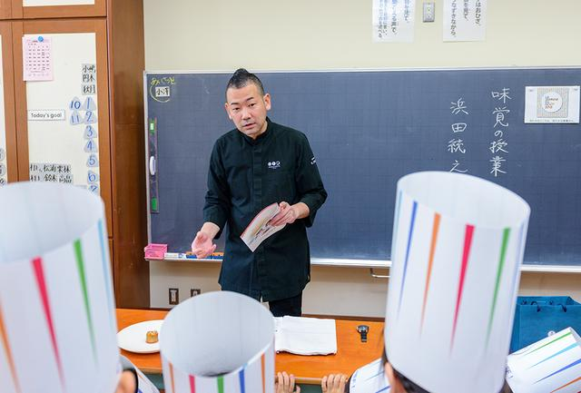 画像: 「星のや東京」料理長の浜田シェフを取り囲む、中央区立明正小学校3年生の子どもたち(2018年当時)。シェフが用意した「りんごのシャルロット」を前に興味津々 COURTESY OF LA SEMAINE DU GOÛT