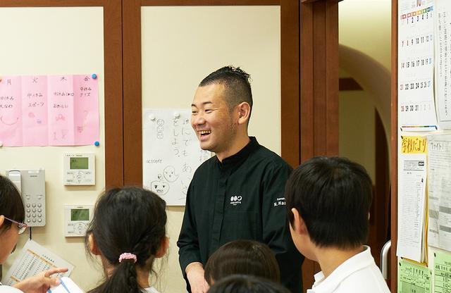 """画像: 浜田統之シェフ。2013年には世界のフランス料理の頂点を競う「ボキューズ・ドール」で日本人で初めて世界3位、魚部門で一位に輝いた日本屈指の料理人。料理長を務める「星のや東京」でも、「酸・塩・苦・辛・甘」の五味を大事に、日本ならではの天然素材とフレンチの技法を使った""""NIPPONキュイジーヌ""""を手がける。授業のあと、子どもたちに囲まれて"""