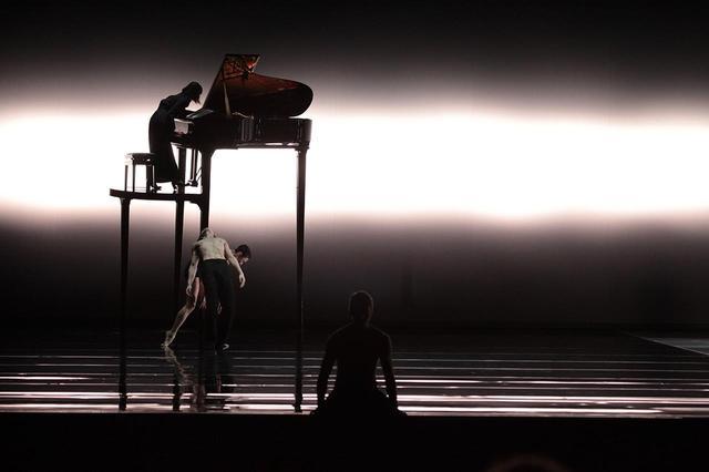 画像: 《Tar and Feathers》 2006 振付家イリ・キリアンのコンテンボラリーダンス作品に、向井山はモーツァルトの曲の演奏で参加。柱のように高くそびえるピアノの脚にダンサーたちが絡む © DJH