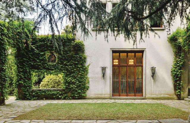 画像: 中庭は一部分が壁で囲まれており、その壁にはルーチョ・フォンタナが陶器で製作した飾り板が埋め込まれている。また、壁に空いた四角い穴から、庭の景色が額縁で切り取ったように見える