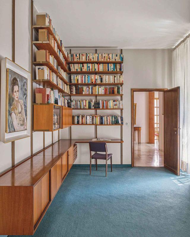 画像: 主寝室と隔てられた部屋には、オズヴァルド・ボルサーニが1957年にデザインした組み立て式の本棚と、エウジェニオ・ジェルリが手がけた椅子がある。どちらもオズヴァルドが双子の兄弟のフルジェンツィオとともに設立した企業、テクノ社で製作された。壁に掛かっているのはフルジェンツィオの妻、カルラ・ボルサーニの肖像画で、画家グイド・タローネの作品だ