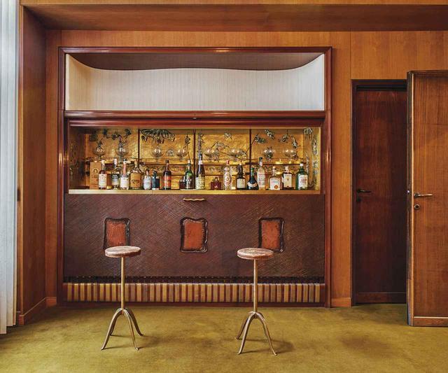 画像: プレイルームには、フォンタナが手がけたセラミックの飾り板をあしらったバーが。その背後は、アドリアーノ・スピリンベルゴが製作した、金メッキを施したガラス製モザイクの壁