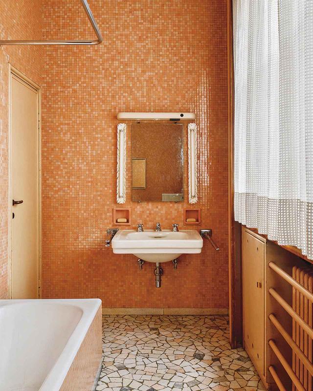 画像: ゲスト用の浴室の壁は、光沢のあるピンク色の陶器製モザイクタイルで覆われている