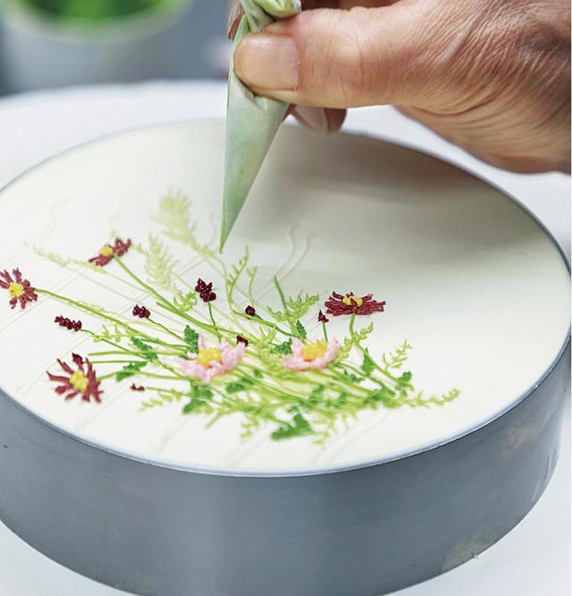 """画像: 季節の花のケーキを、というオーダーに、武藤さんが描いたのは、秋の野原に咲く2色のコスモスとシックなワレモコウ、ススキの取り合わせだった。花の選択も構図からも、華道や日本画に通じる侘びた気配が漂う。最初に引いた線は、花と草の背景にある細い横線。大和絵の""""すやり霞""""を彷彿とさせる。見た目に濃厚なクリームは、口に含んだ途端に溶けて広がり、後味はごくさわやか"""