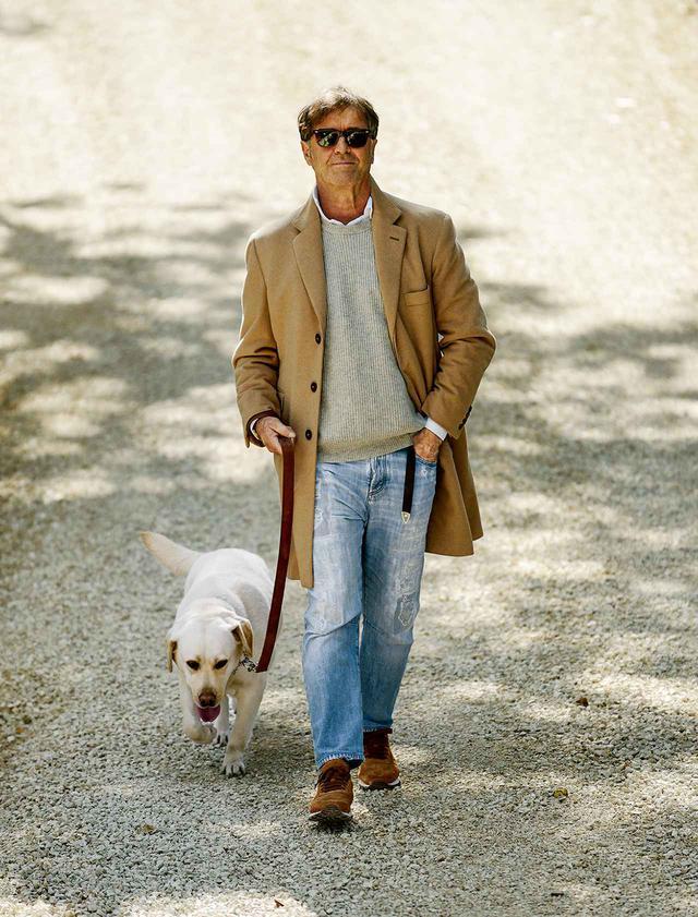 画像: BRUNELLO CUCINELLI(ブルネロ・クチネリ) 「ソロメオの村を散歩する愛犬ヴィオラと私。この写真の色のトーンは最高。ラブラドールのヴィオラの白い毛が、ほどよく薄汚れた色になっている。私の装いは、スニーカーもデニムも、すべて自分がデザインしたもの。コートは23年前から愛用している」 COURTESY OF BRUNELLO CUCINELLI