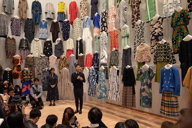 """画像: 約400点の衣服を、まさに森のように配した「森」の展示室。流行にとらわれない服づくりというミナ ペルホネンの理念に基づき、制作されたシーズンを区別せず、展示されている。真ん中に立つのはデザイナーの皆川明。展示構成は建築家の田根剛、グラフィックデザインは葛西薫が担当。こうした過去の展覧会に関わってきたクリエイターとも""""つづく""""を共有しながら、本展は構成されていると皆川は話す PHOTOGRAPH BY FUMINARI YOSHITUGU"""