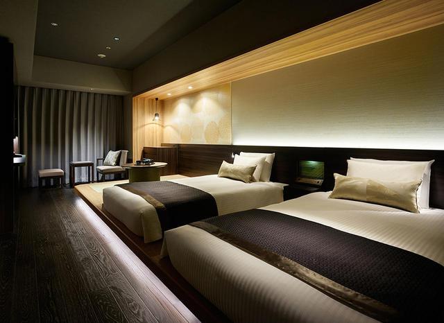 画像: 「デラックスツイン」<34.6㎡> 琉球畳の敷かれた小上がりにベッドが置かれたシックな客室。外国人観光客にも人気