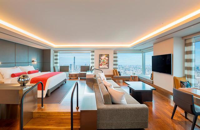 画像: 「デザイナーズスイート」<100㎡> ベッドが一段高い位置に。大理石造りのバスルームも広く高級感満載