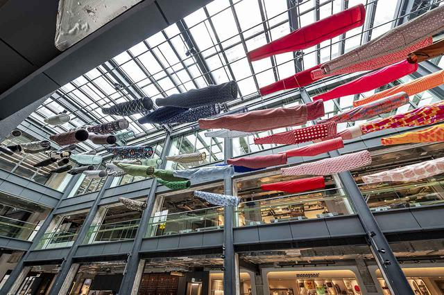 画像: 『須藤玲子の仕事-NUNOのテキスタイルができるまで』の展示風景から。CHATがある文化とビジネスの複合施設商業施設The Millsの中庭には、須藤がデザインした《こいのぼり》が宙を舞う © CHAT, HONG KONG