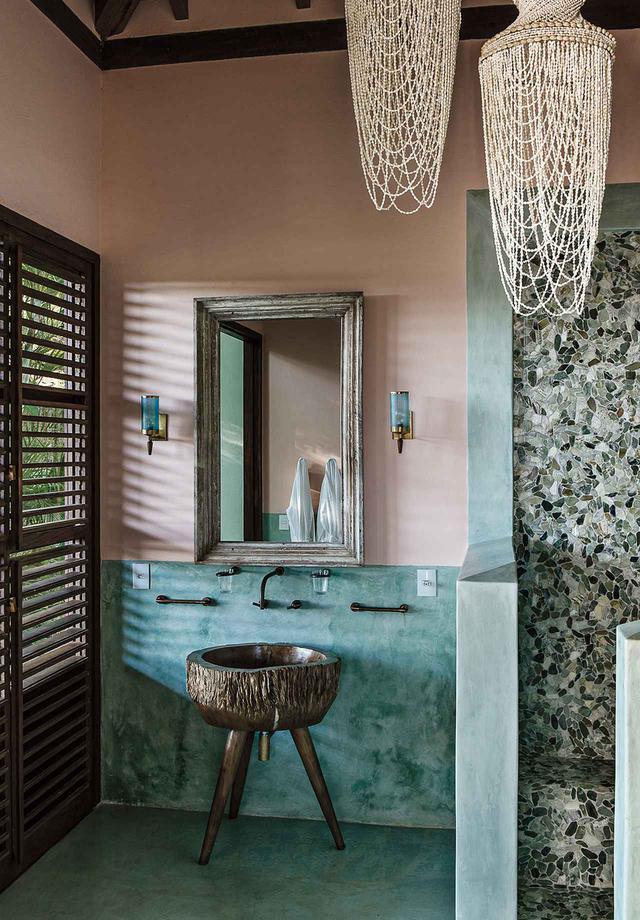 画像: ゲスト用バスルーム。「ウーシュー」の再生材で作った鏡。地元のアーティストがペキー(フルーツ)の木で作った3本脚のシンク