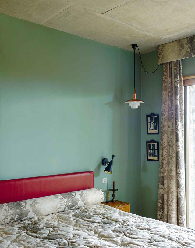 画像: 天井から下がっているのはデンマークのデザイナー、ポール・ヘニングセンが考案したペンダント型の照明で、ルイス・ポールセン社製造。その下の壁に飾られているのは、1968年に撮影されたイギリス女王エリザベス2世とフィリップ殿下の写真。カーテンとベッドカバーはニナ・キャンベルのファブリック