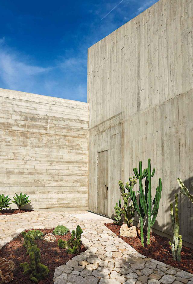 画像: 玄関に通じる小道には地元で取れる石が敷かれ、模様をあしらったコンクリート製の壁に溶け込むように配置されている