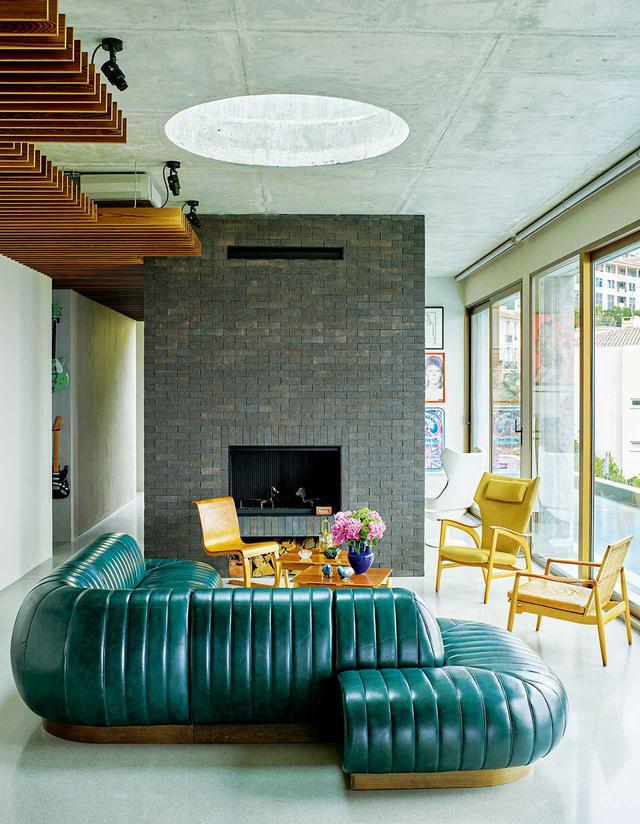 画像: リビングルームに置かれたスカンジナビア製の椅子と、トム・ディクソン製作の特注ソファ
