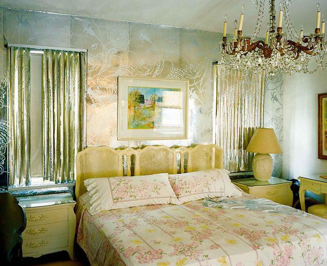 画像: 主寝室。夫妻が愛用したベッドリネンと妻のナイトガウンが見える。シルバーの壁紙に反射してクリスタルのシャンデリアはきらめきを増す
