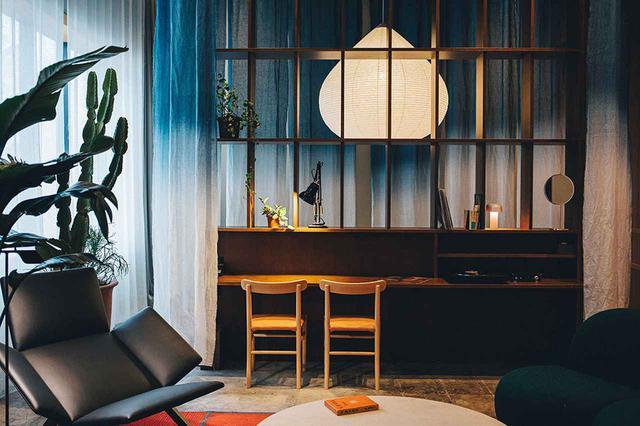 """画像: 「K5 Loft」<80㎡> 最上級スイートルーム。4.5mの天井高も印象的。植物が置かれ、ダイニングテーブルやミニキッチンも設えられている。採光も充分、""""新しさとアンティーク""""調和が美しいK5のフラッグシップ"""