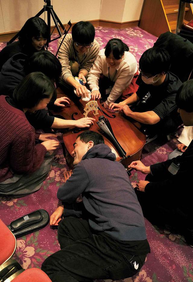 画像: 「5分間で4種類の音を出してみよう」。藤倉(写真手前)の呼びかけで、コントラバスのメンバーたちが弦を弾いたり、裏をこすって音を立てたり。教える側、教えられる側の別なく音と戯れ、創造を楽しむ