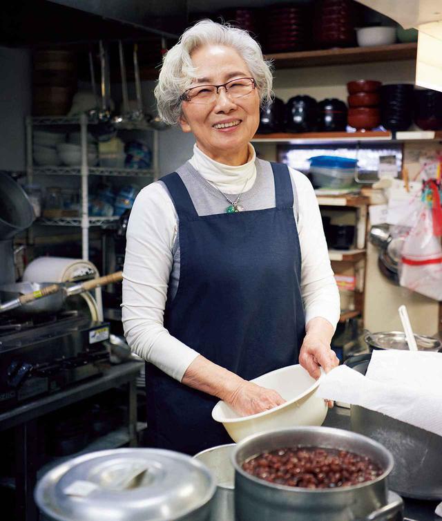 画像: 厨房で料理をする店主の森田享子さん。「母に『大根1本買って10種類のおかずを作れるようになったら楽に暮らせる』とよく言われました。今の方たちにもそういうことを伝えたいですね」